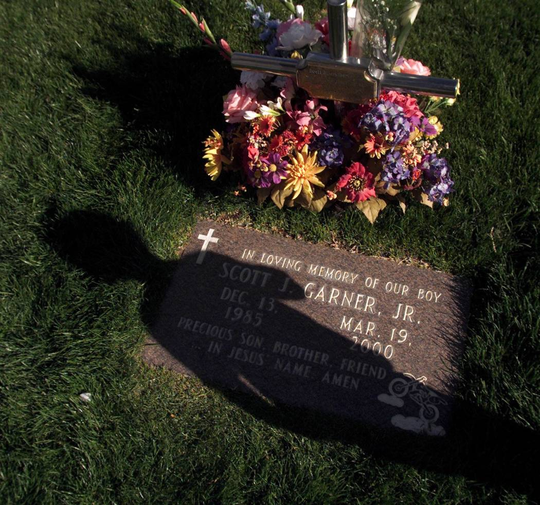 A shadow cast over the grave stone of Scott Garner Jr. on March 19, 2002. Garner and five other ...
