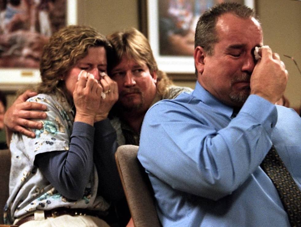 Doug Gould embraces his wife Viola and Dale Booth wipes his eyes while listening to Clark Count ...