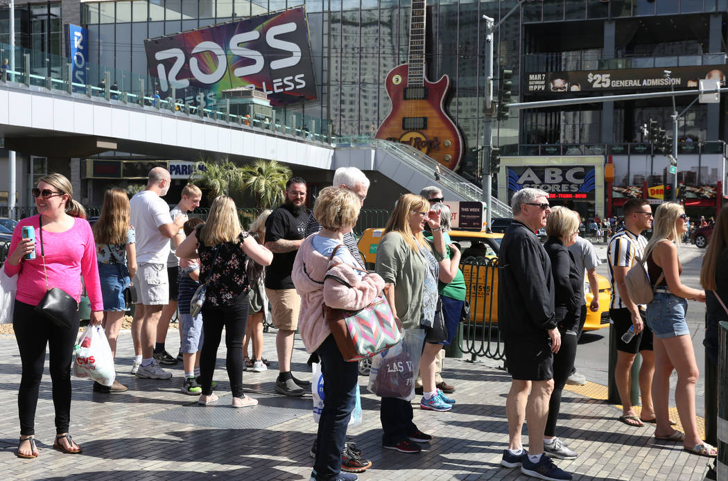 Tourists wait at a traffic lights as they walk along Las Vegas Boulevard on Friday, March 6, 20 ...