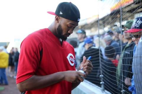 Cincinnati Reds pitchers Amir Garrett signs an autograph during a live batting practice event a ...
