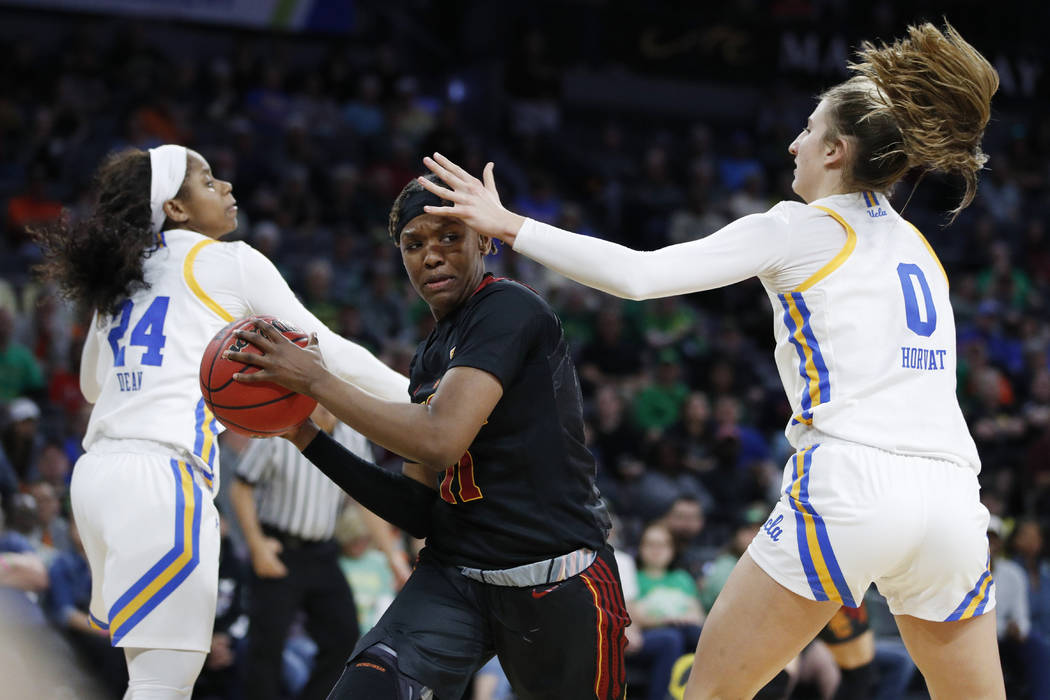Southern California's Aliyah Jeune (11) passes around UCLA's Chantel Horvat (0) during the seco ...