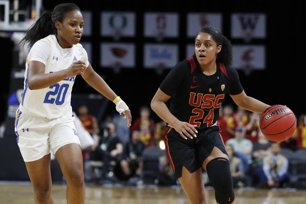 Southern California's Desiree Caldwell (24) drives around UCLA's Charisma Osborne (20) during t ...