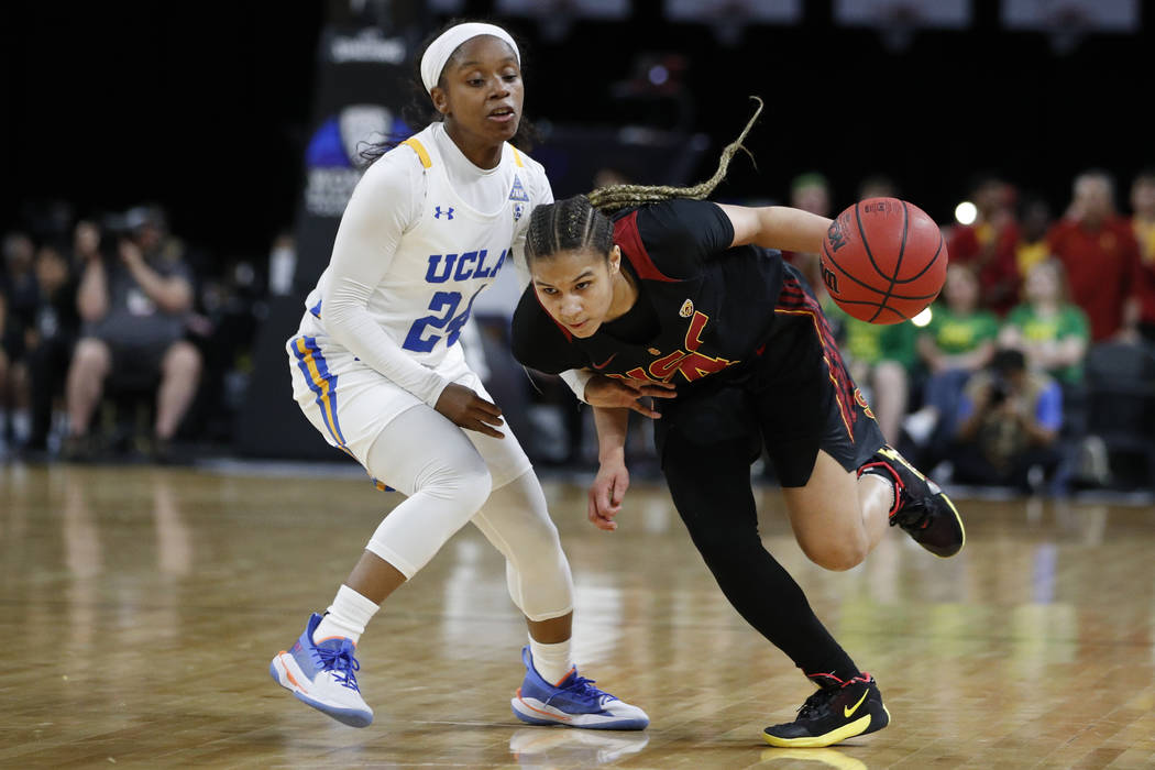 Southern California's Endyia Rogers (4) drives around UCLA's Japreece Dean (24) during the firs ...