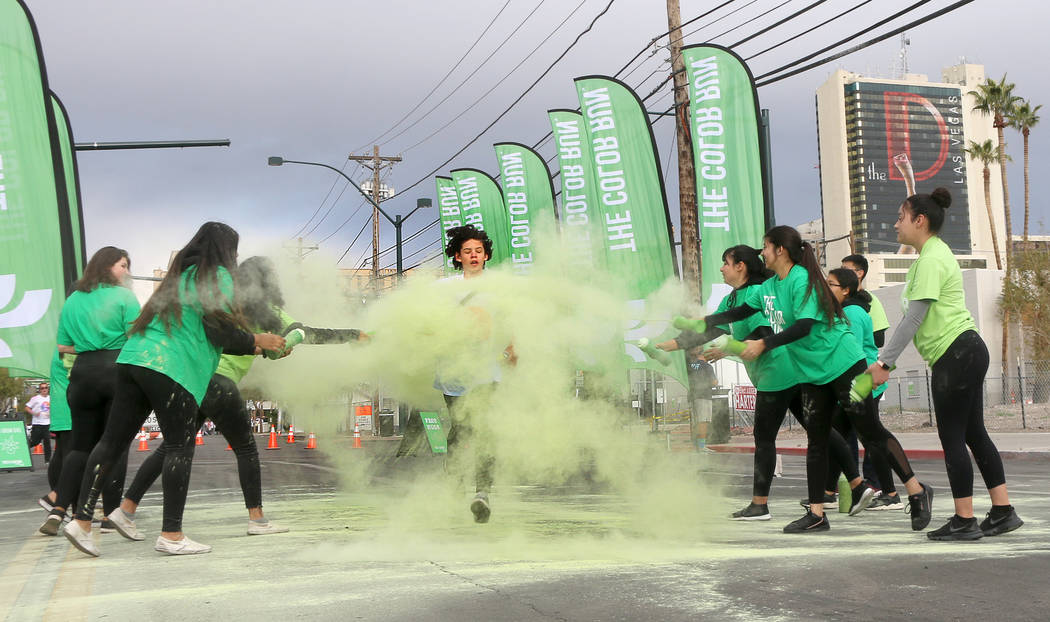 A runner is covered in green powder as he makes his way through one of several Color Run colori ...