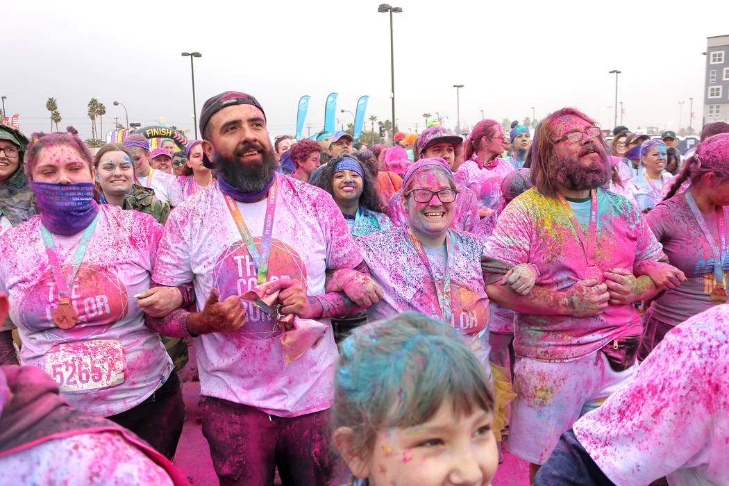 Color Run participants link arms and dance to music at the end of the run. (Anton)