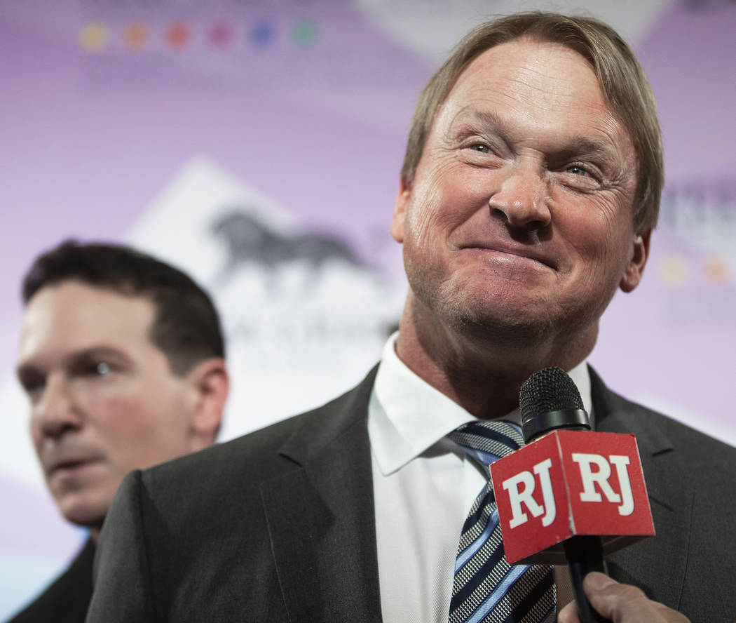 Raiders head coach John Gruden, right, talks with the media on the red carpet during the 24th A ...
