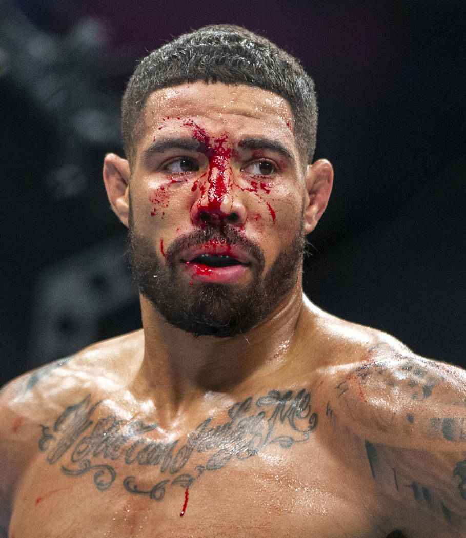 Welterweight Max Griffin is bloodied as he battles Alex Oliveira during the second round their ...