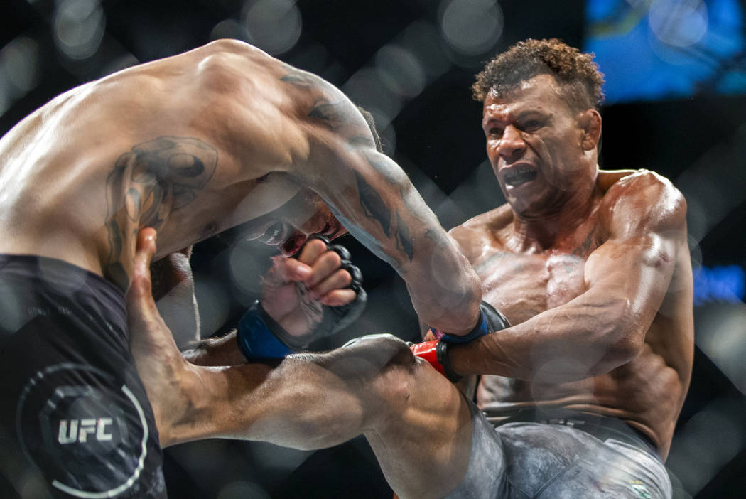 Welterweight Max Griffin, left, takes a kick to the stomach from Alex Oliveira during the third ...