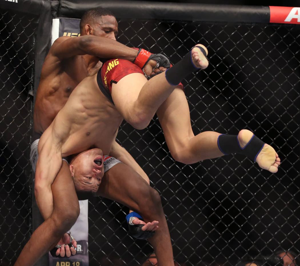 Welterweight Neil Magny, left, attempts to lift up Li Jingliang during the second round of thei ...