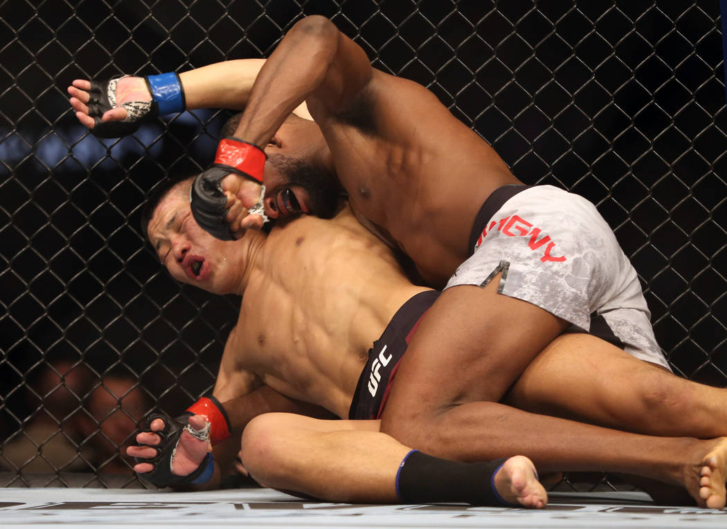 Welterweight Li Jingliang, left, is punched in the face by Neil Magny during the third round of ...