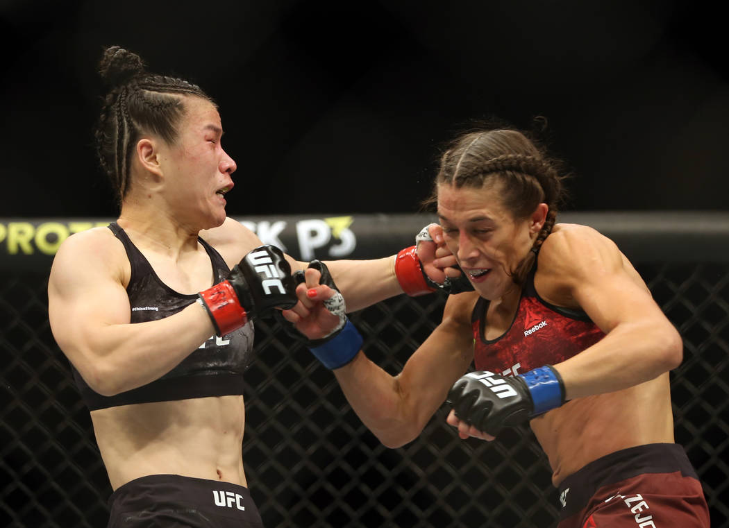 WomenÕs Strawweight Weili Zhang, left, connects on a punch on Joanna Jedrzejczyk during th ...