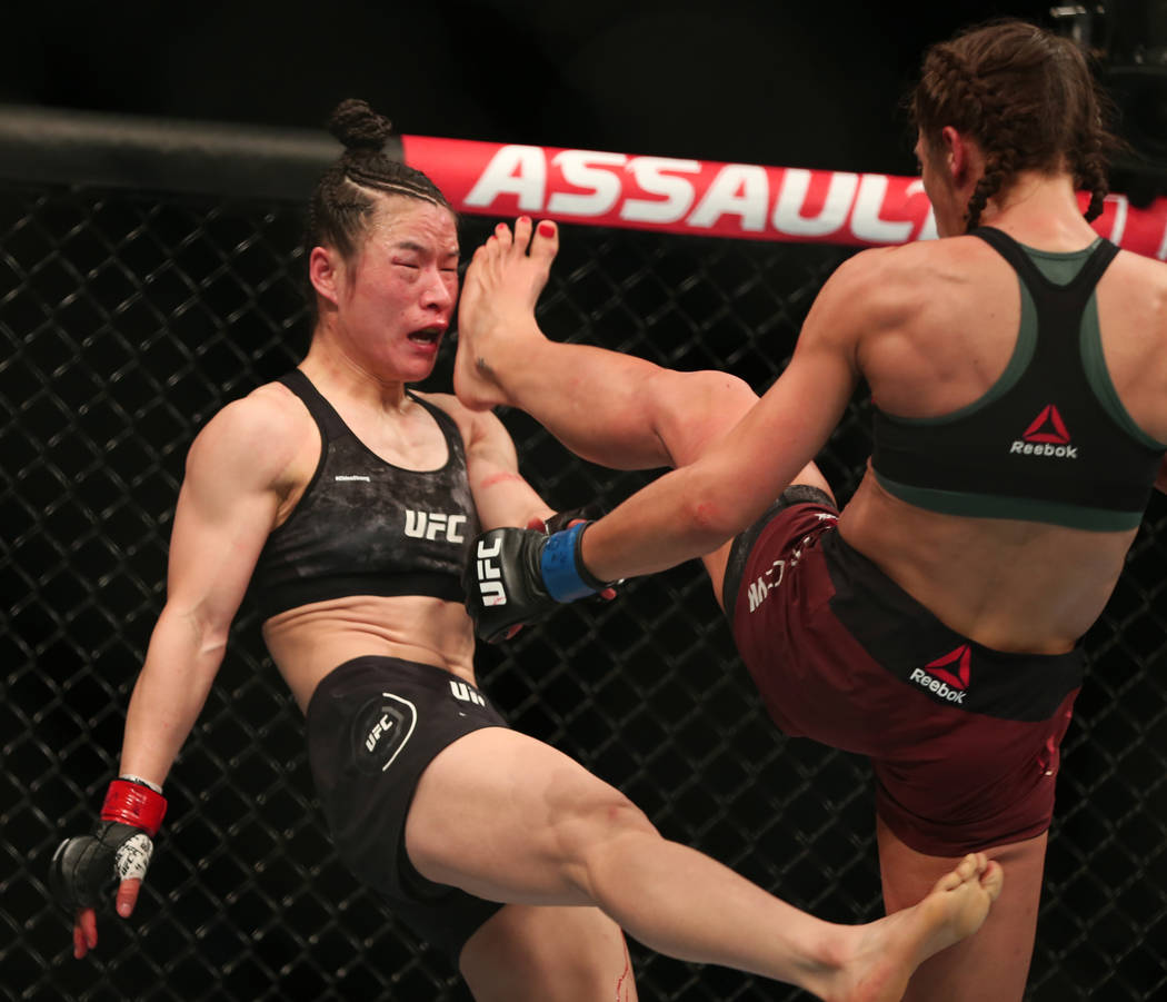WomenÕs Strawweight Weili Zhang, left, and Joanna Jedrzejczyk trade kicks during the third ...