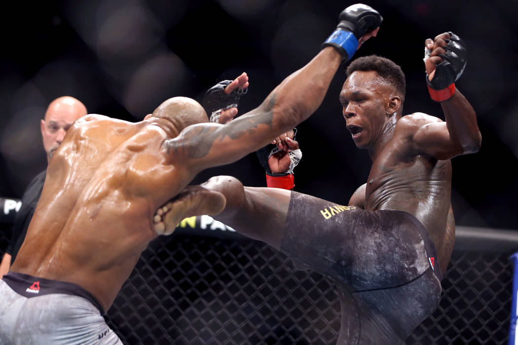 Middleweight Yoel Romero, left, is kicked by Israel Adesanya during the second round of their U ...