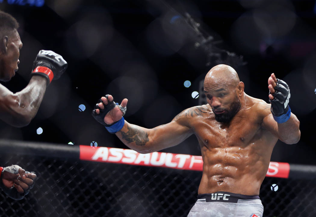 Middleweight Israel Adesanya, left, looks to Yoel Romero who attempts to draw him in during the ...