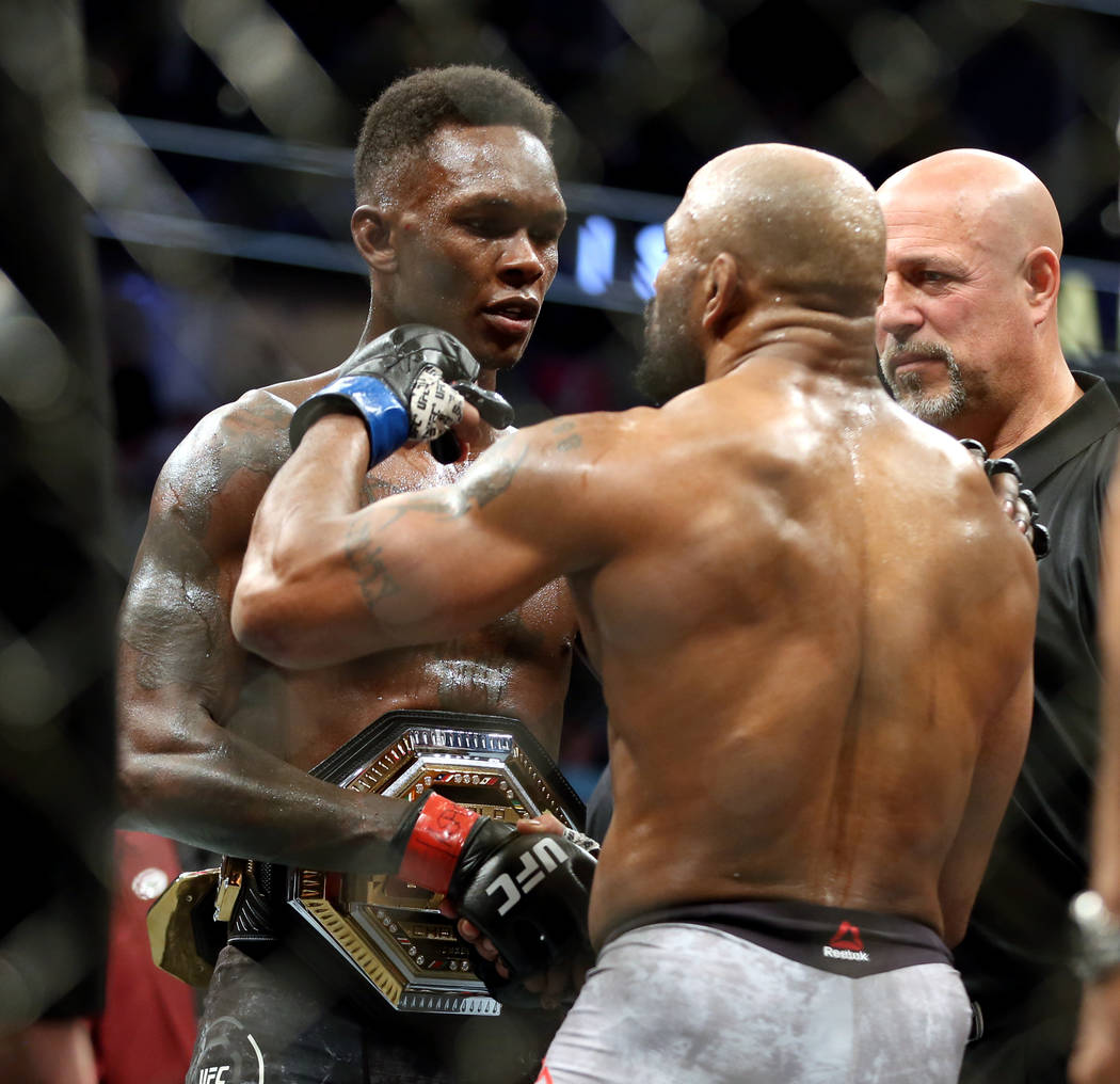 Middleweight Israel Adesanya , left, and Yoel Romero come together after Adesanya is awarded th ...