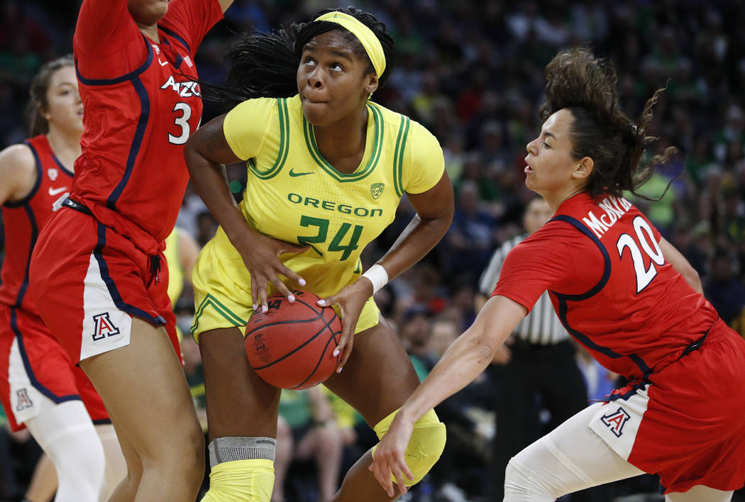 Oregon's Ruthy Hebard (24) drives around Arizona's Dominique McBryde (20) during the second hal ...