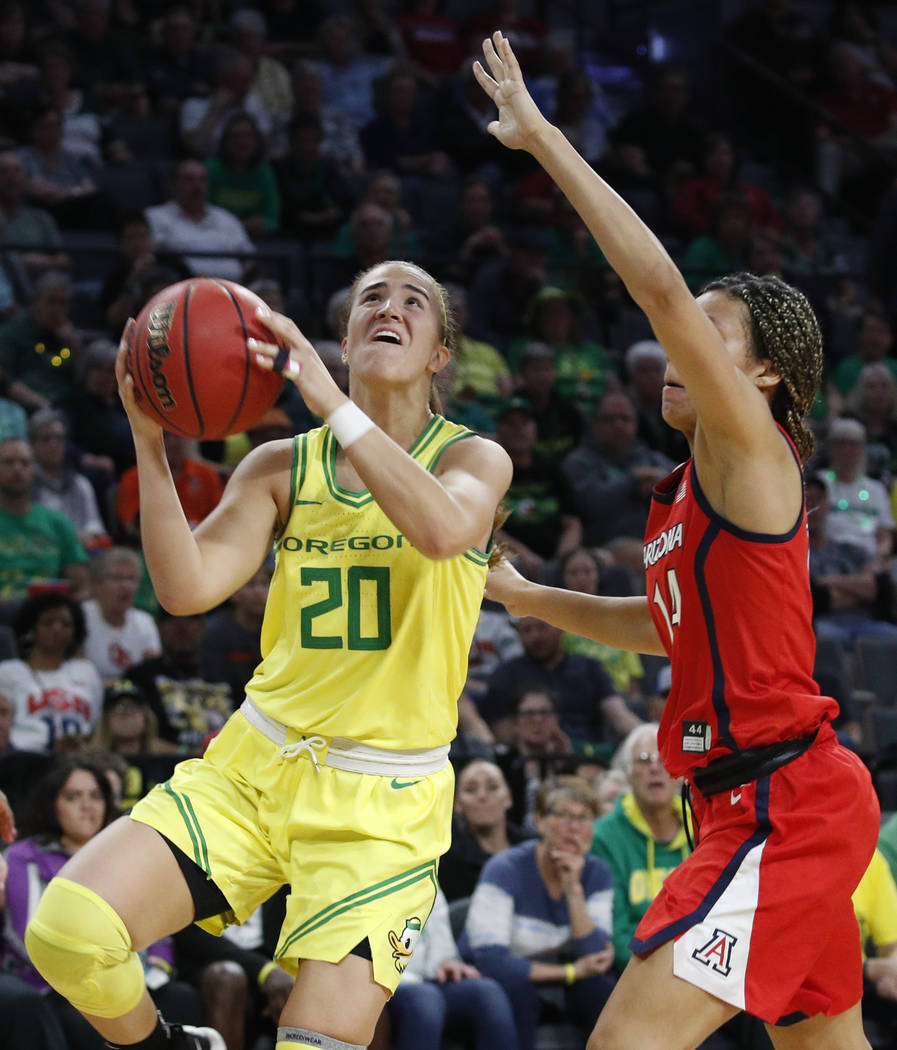 Oregon's Sabrina Ionescu (20) shoots around Arizona's Sam Thomas (14) during the second half of ...