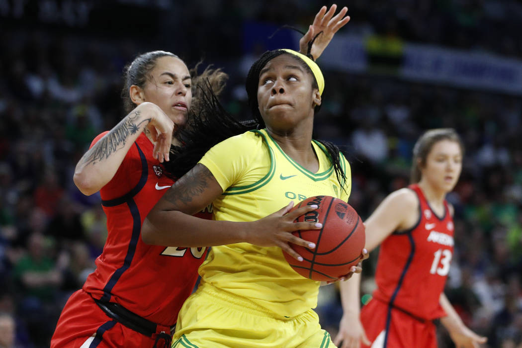 Oregon's Ruthy Hebard (24) drives into Arizona's Dominique McBryde (20) during the second half ...