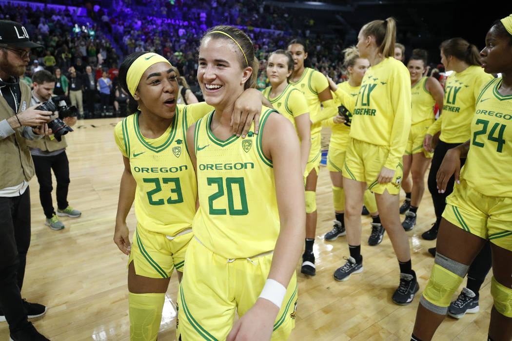 Oregon's Minyon Moore (23) and Sabrina Ionescu (20) walk off the court after defeating Arizona ...