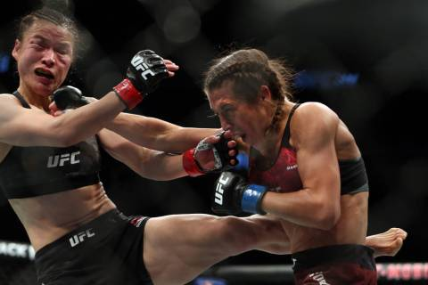 Weili Zhang, left, and Joanna Jedrzejczyk trade blows during the third round of their UFC 248 f ...