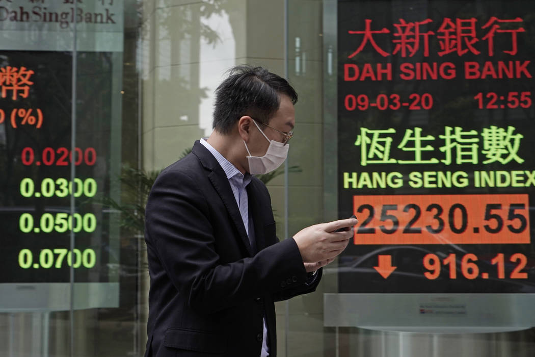 A man walks past an electronic board showing Hong Kong share index outside a local bank in Hong ...