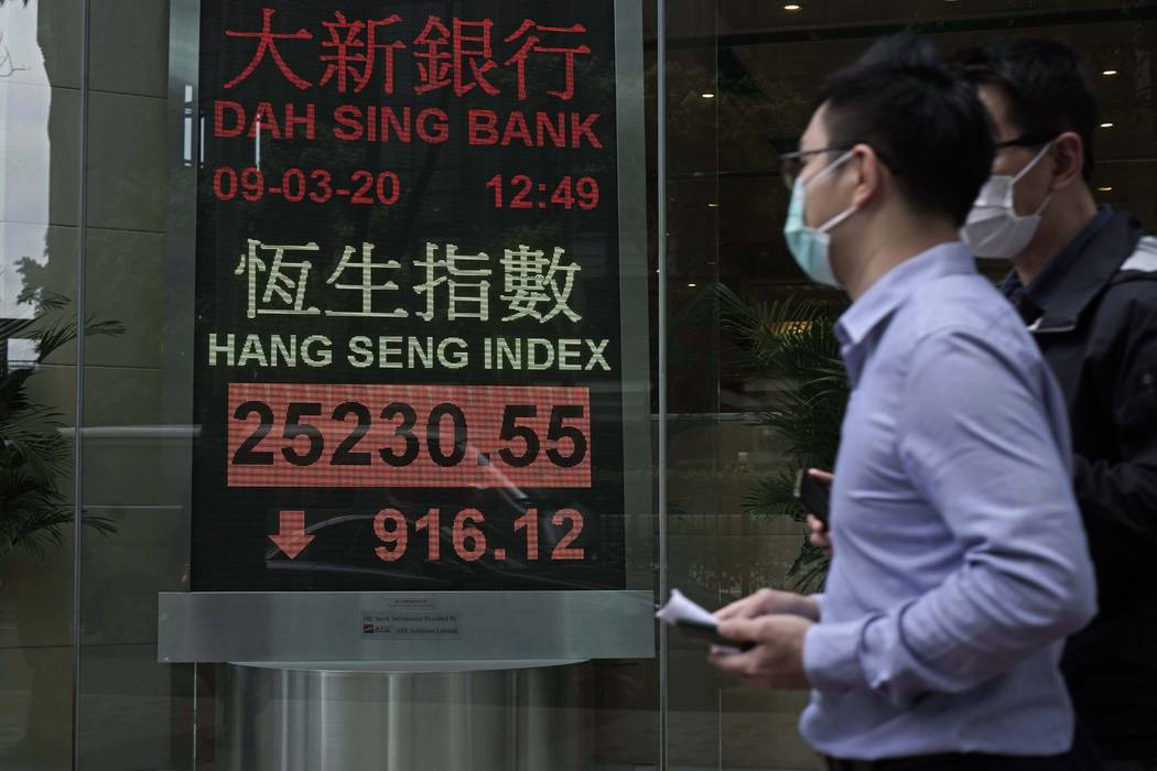 People walk past an electronic board showing Hong Kong share index outside a local bank in Hong ...
