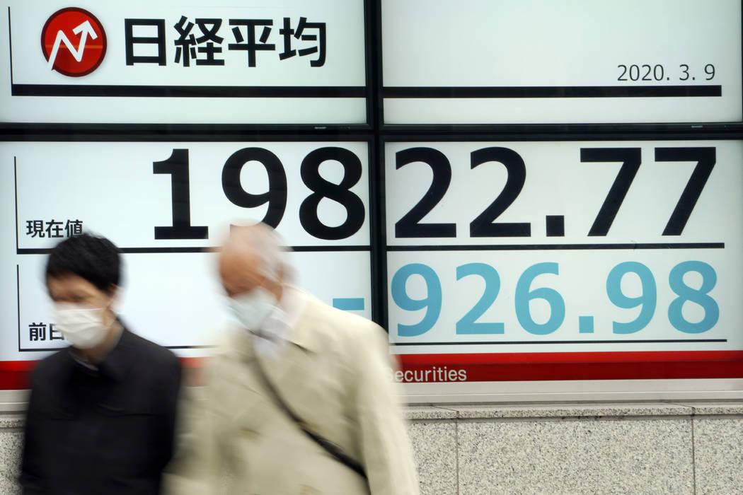 Men walk past an electronic stock board showing Japan's Nikkei 225 index at a securities firm i ...