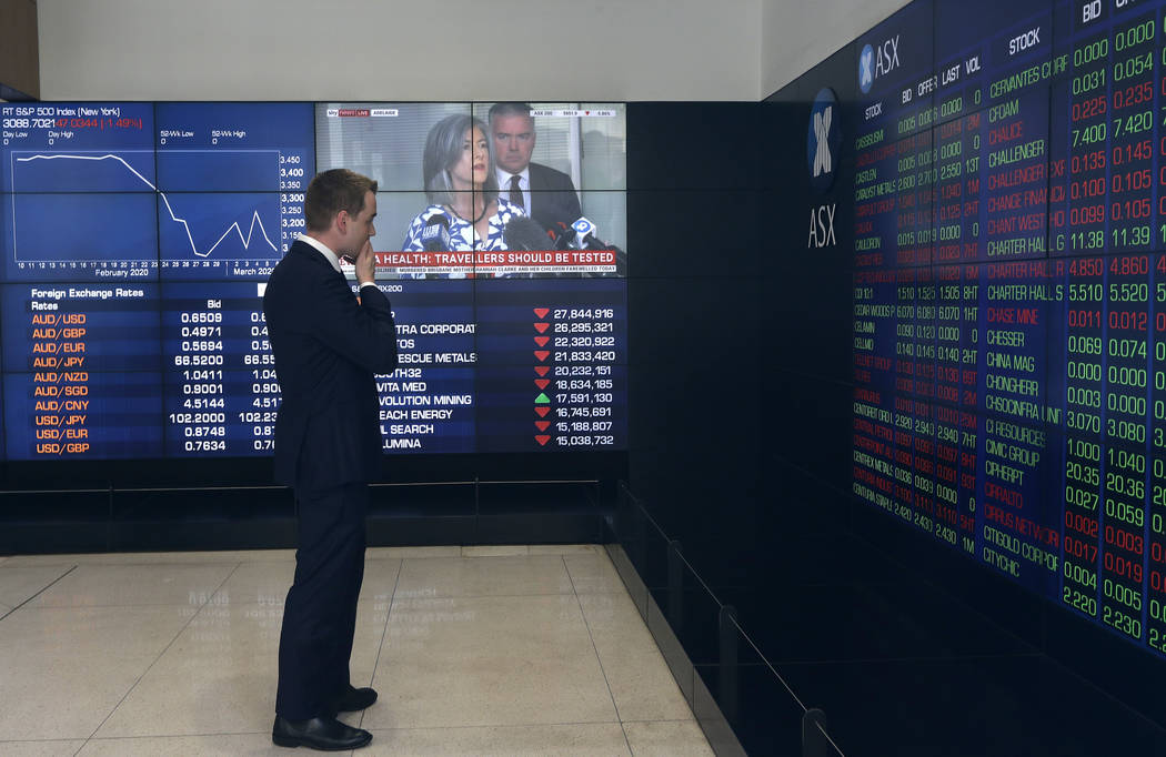 A man stands in the viewing gallery at the Australian Stock Exchange in Sydney, Monday, March 9 ...