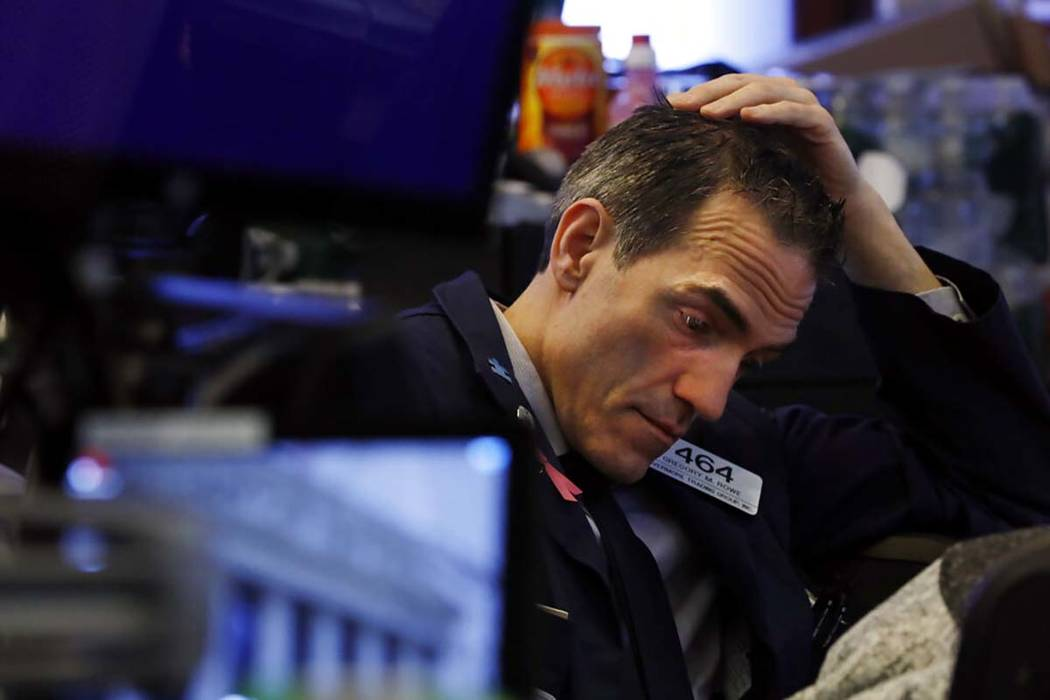 Trader Gregory Rowe prepares for the day's activity on the floor of the New York Stock Exchange ...