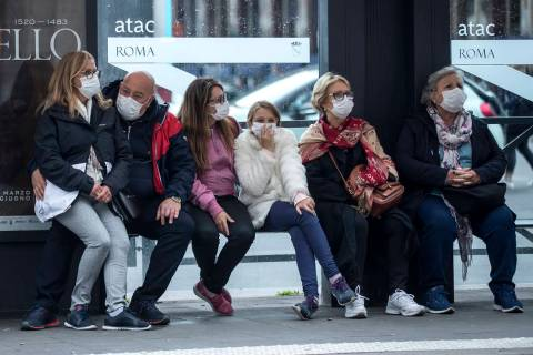 People wait at a bus stop, in Rome, Monday, March 9, 2020. Italy announced a sweeping quarantin ...