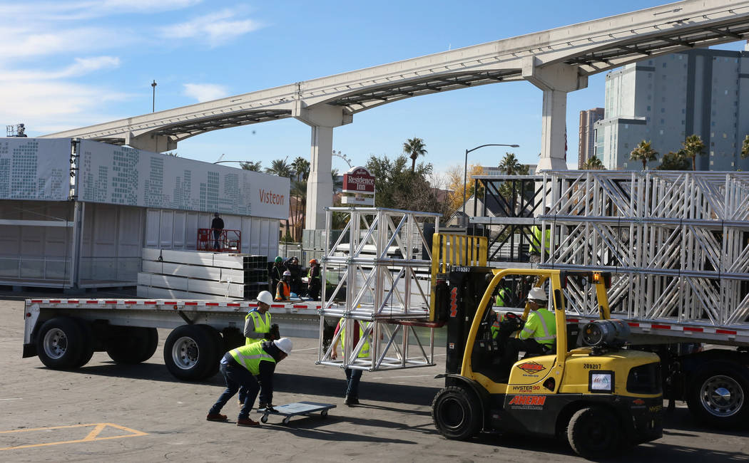 Workers from Pavillon Event Service unload construction equipments next to the Visteon's, a glo ...