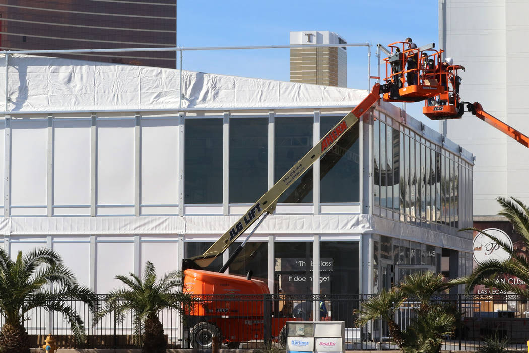 Workers install the APTIV's, a global technology company, booth ahead of CES on Friday, Dec. 2 ...