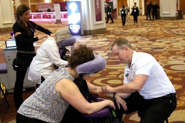 Las Vegas massage therapist Ling Cooley, left, works on Laura Hendrix of Waco, Texas, while Tro ...