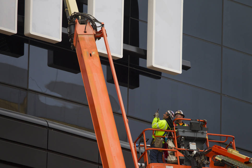 A worker takes a photo after helping install the last letter in the signage for the Raiders All ...