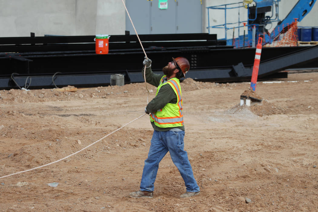 A worker helps in the installation of the last letter in the signage for the Raiders Allegiant ...