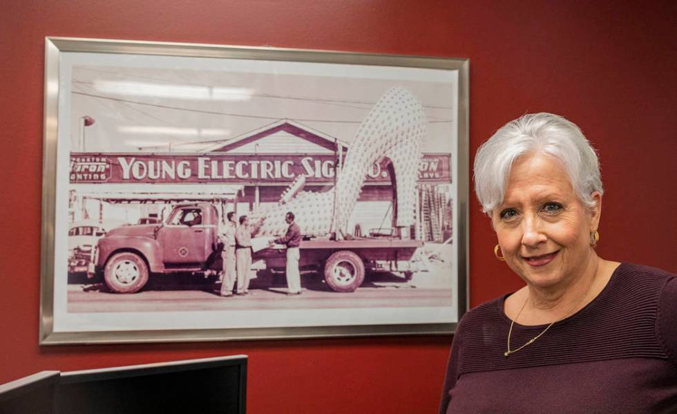 Administrative assistant for Yesco Karin Tomanio stands next to a photograph of her grandfather ...