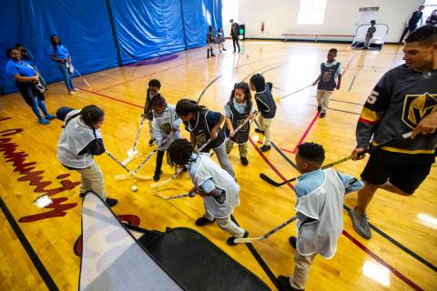 Children vie for the ball during a youth street hockey clinic at Doolittle Recreation Center in ...