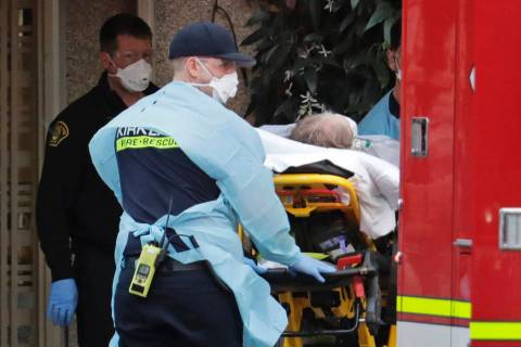 A patient is loaded into an ambulance, Tuesday, March 10, 2020, at the Life Care Center in Kirk ...