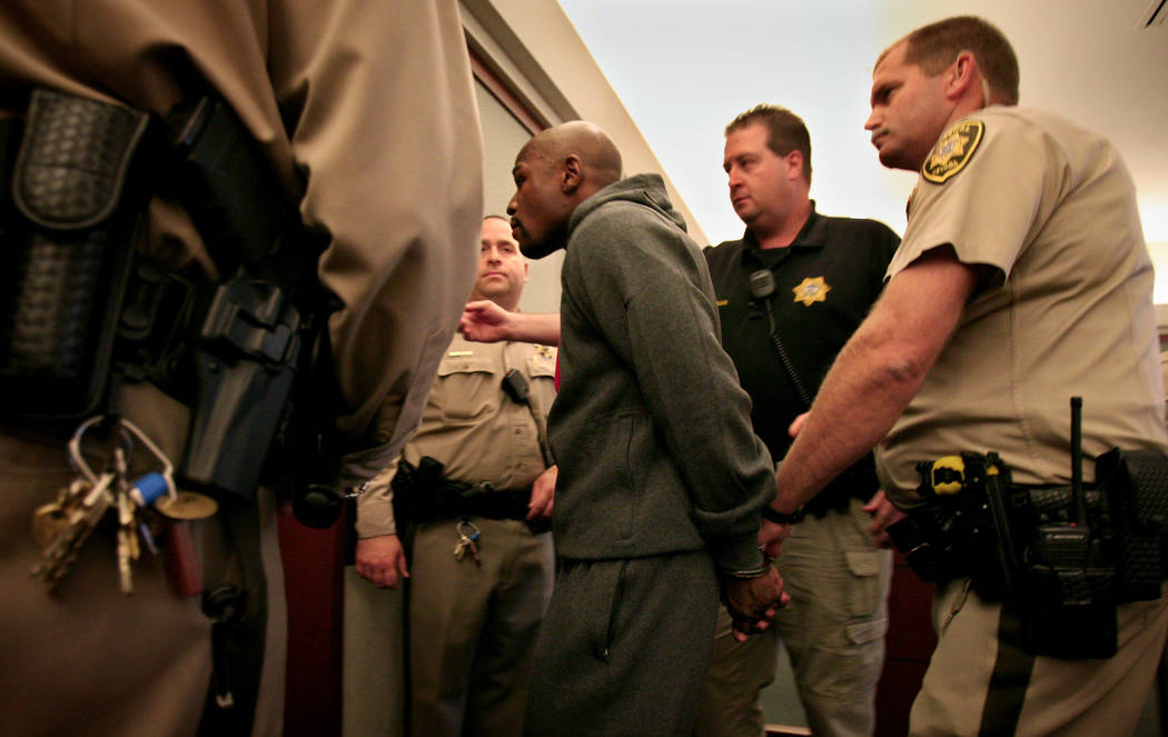 Officers escort boxer Floyd Mayweather Jr. out of Regional Justice Center courtroom Friday, Jun ...
