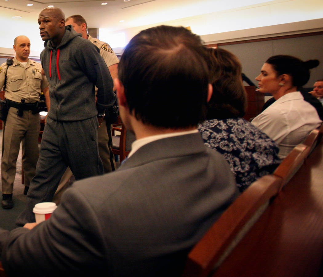 Officers escort boxer Floyd Mayweather Jr. out of courtroom at the Regional Justice Center Frid ...