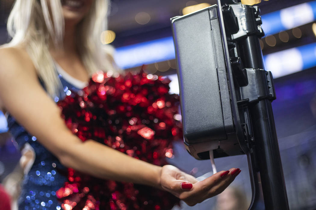 A University of Arizona cheerleader uses hand sanitizer after the game against University of Wa ...