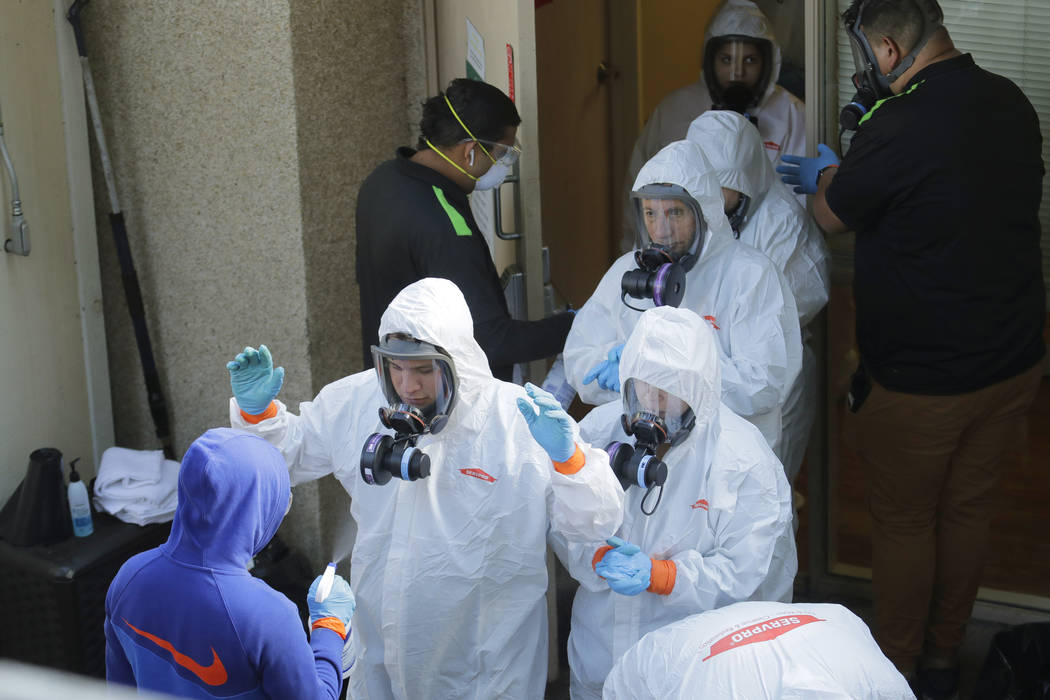 Servpro cleaning workers are sprayed as they exit the Life Care Center in Kirkland, Wash., Thur ...
