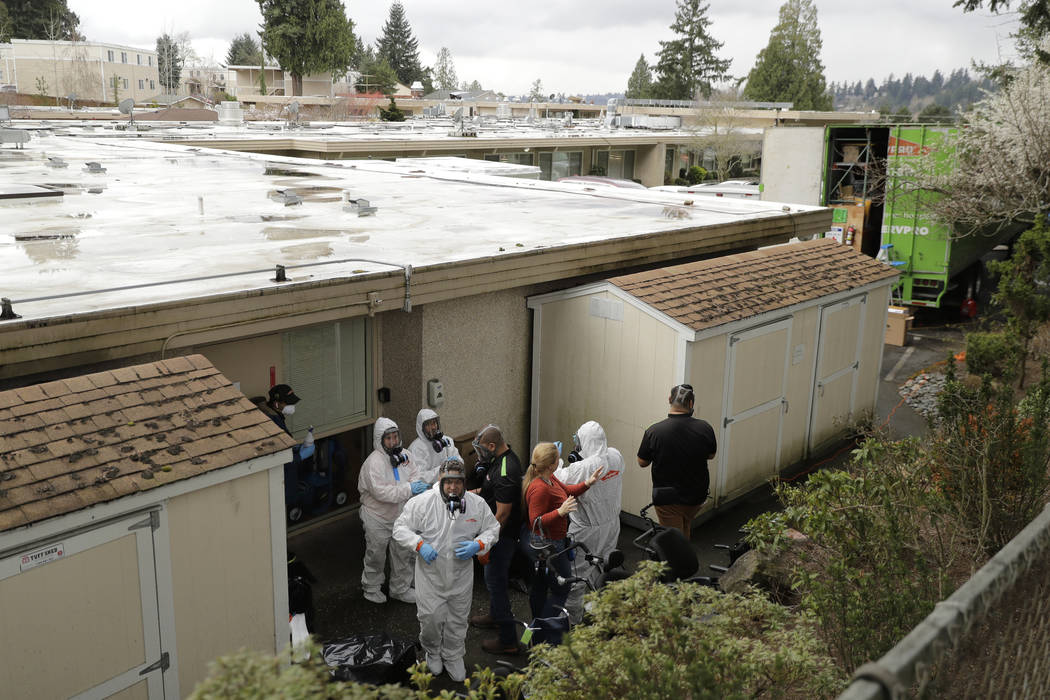 Servpro cleaning workers prepare to remove their protective gear as they exit the Life Care Cen ...