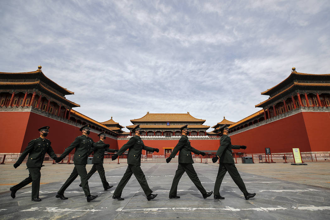 Soldiers wearing protective face masks march past the closed entrance gates to the Forbidden Ci ...