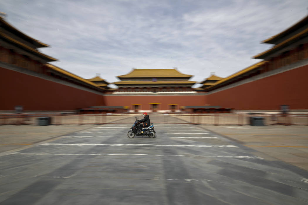 A man rides on an electric-powered scooter passes by the closed entrance gates to the Forbidden ...