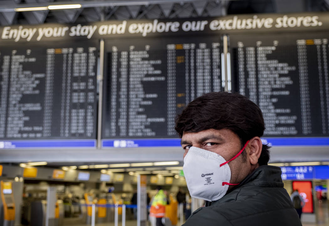 A passenger from India waits for his flight in a terminal at the airport in Frankfurt, Germany, ...