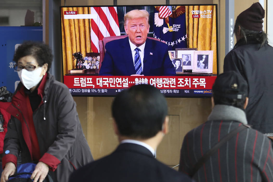 People watch a TV screen showing a live broadcast of U.S. President Donald Trump's speech at th ...