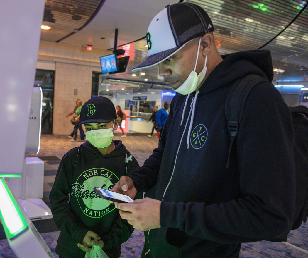Christian Pabalate, 11, and his father, Nicholas Johnson, of San Francisco, print tickets durin ...