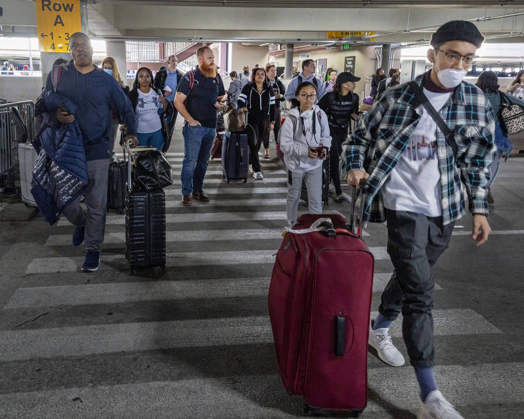Passengers walk to the ride-hailing service area at McCarran International Airport in Las Vegas ...