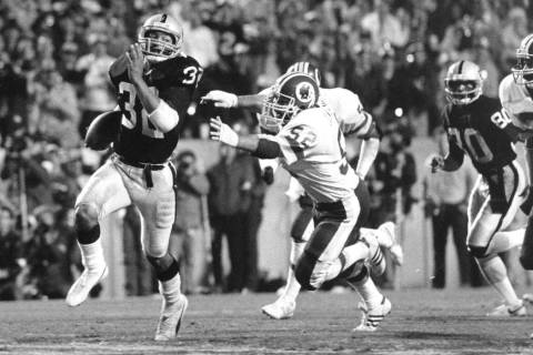 In this Jan. 22, 1984, file photo, Los Angeles Raiders running back Marcus Allen (32) outruns W ...